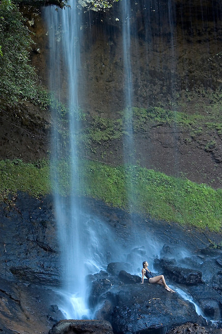A pretty girl is enjoying the biggest waterfall in Palau, Micronesia