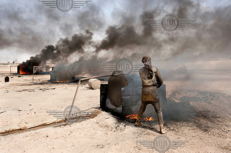 A man refines oil to produce petrol and diesel. A petrol production micro-industry has grown up around the desert town of Al Mansura east of Al Raqqah, the capital of the Islamic State. Small stills burn oil that is trucked in by the barrel load from the oil fields of Al Hasakah. Each still can process about a thousand litres of crude a day into petrol and diesel. The Islamic State has taken oil fields from Syrian rebels and the government in recent months. They are believed to control hundreds of wells, an important source of income for the Islamists and depriving Syrian President Bashar al-Assad's government of a major source of income.