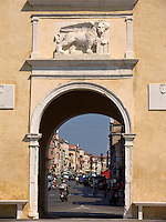 City entrance gate with Lion of St. Mark frames main street of Chioggia Ital