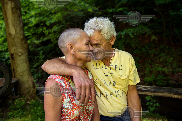 """Charlie Branham, a former coal miner, poses with his wife Donna outside their home in Lenore, West Virginia. Donna Branham shaved her head on the steps of the West Virginia Capitol with a group of women in protest to mountaintop-removal mining. The shaving of their heads was symbolic of the mountains that have been stripped of all of the living things on them. It was also symbolic of the many people who are sick or dying as the result of Mountaintop Removal. Mountaintop Removal is a method of surface mining that literally removes the tops of mountains to get to the coal seams beneath. It is the most profitable mining technique available because it is performed quickly, cheaply and comes with hefty economic benefits for the mining companies, most of which are located out of state. It is the most profitable mining technique available because it is performed quickly, cheaply and comes with hefty economic benefits for the mining companies, most of which are located out of state. Many argue that they have brought wage-paying jobs and modern amenities to Appalachia, but others say they have only demolished an estimated 1.4 million acres of forested hills, buried an estimated 2,000 miles of streams, poisoned drinking water, and wiped whole towns from the map. """"People don't know how hard it is on the Appalachian people,"""" Branham said of mountaintop-removal mining. """"They have no idea. And they don't want to know. As long as they don't have to look at it, they can ignore it."""""""