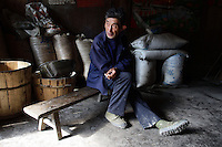 A man in his home in a remote village in the mountains of Pingwu County in Sichuan Province, south-west China.