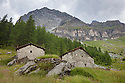 Ruined farm buildings in mountain landscape, Aosta Valley, Monte Rosa Massif, Pennine Alps, Italy. July.
