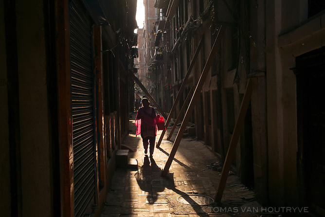 A woman walks through a narrow alley where quake-damaged homes are propped up with wooden braces in Kathmandu, Nepal in June 2015.