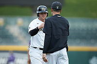 Brendan Tinsman (9) of the Wake Forest Demon Deacons bumps fists with third base coach Tom Walter (16) during the game against the Furman Paladins at BB&T BallPark on March 2, 2019 in Charlotte, North Carolina. The Demon Deacons defeated the Paladins 13-7. (Brian Westerholt/Four Seam Images)