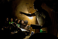 René Justin Danssou helps children study at night, reading by the light of a Chinese made solar powered lamp that cost 25,000 CFA (GBP 34.00). The village, of 11,000 people, has no access to the electricity grid.