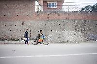 A man carries food on his bicycle on a street of Kathmandu, Nepal.