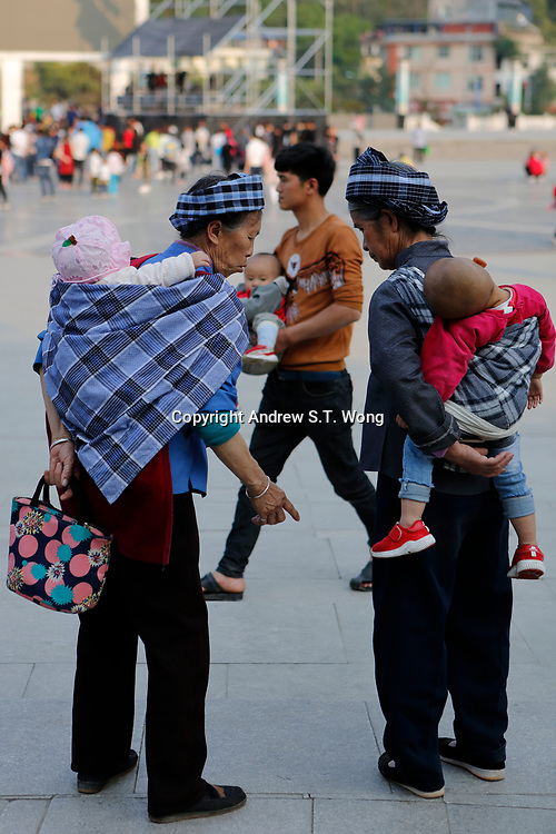 Elderly women of the ethnic Bouyei Tribe take care of their grandchildren at Wangmo County in China's southwestern Guizhou Province, April 2019.