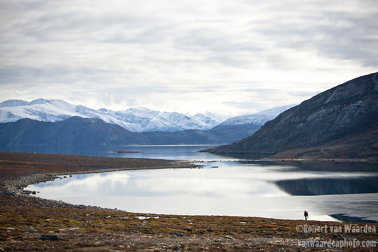A lone figure in an immense landscape, Baffin Island, Nunavut, Canada. In the background, the snow covered mountains of Baffin Island.