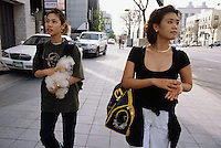 """Korea. South Korea. Seoul.  Two young teenage girls carry their pets in the streets. They are going to the dog cafe, know as  """"Fusion dog mania cafe"""".  Korean people go there to eat, drink and relax themselves among hundred dogs which are there for the customers. People can love and choose among various dogs the ones they want to hold or pat.  Dogs are perceived as friendly companionship. © 2002 Didier Ruef"""