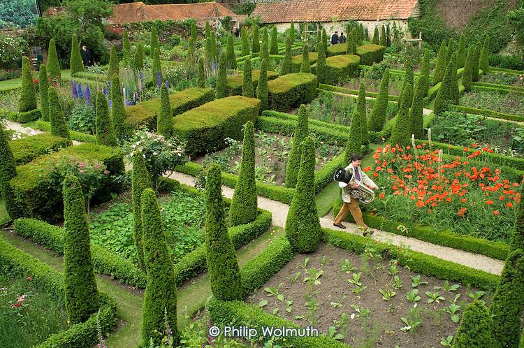 A musician walks through the ornamental garden at Garsington Manor, Oxfordshire, before a rehearsal of Garsington Opera.