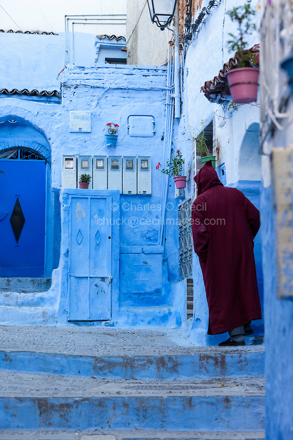 Chefchaouen, Morocco.  Man Standing in Entranceway to his House.  Neighborhood Electric Meters on wall in front.