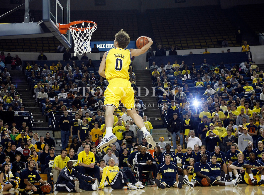 """Michigan guard Zack Novak competes in a slam dunk contest against teammates during the college basketball team's """"Michigan Madness"""" festivities at Crisler Arena, Friday, Oct. 16, 2009, in Ann Arbor, Mich. (AP Photo/Tony Ding)"""