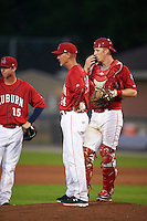 Auburn Doubledays manager Gary Cathcart (24) makes a pitching change as Matthew Page (15) and Erik VanMeetren (13) look on during a game against the State College Spikes on July 6, 2015 at Falcon Park in Auburn, New York.  State College defeated Auburn 9-7.  (Mike Janes/Four Seam Images)