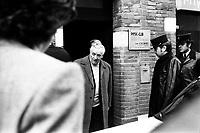 """Picard, Me Cathala, Me Bouscatel, Me Rastoul"""". 14 rue d'Aubuisson. 30 novembre 1976. plan 3/4 de face de Claude Birague sortant de chez lui ; à droite policiers. Cliché pris le jour d'une reconstitution judiciaire dans le cadre de l'affaire du meurtre de René Trouvé. Observation: Affaire René Trouvé-Birague : le 19 février 1976, le journaliste René Trouvé est assassiné d'une balle dans la tête, par deux inconnus, alors qu'il regagne son domicile au 33 rue Bayard."""