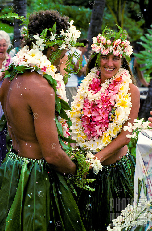 A happy wedding couple wearing in plumeria leis and ti leaf skirts join hands while petals are scattered on them.