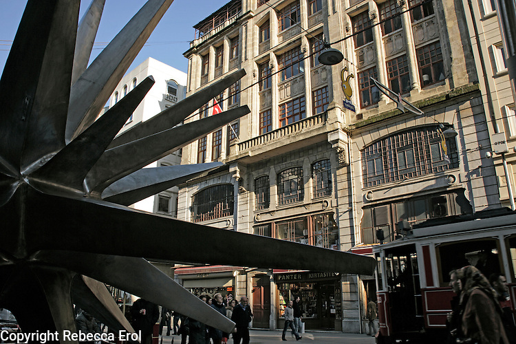 Istiklal Street with the historical tram and historical architecture and modern sculpture in the foreground, Beyoglu, Istanbul, Turkey