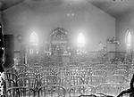 EASTER DECORATIONS IN QUINN CHAPEL, AFTER 1915. John Johnson and his wife, Odessa, were members of Quinn Chapel. Here he photographed the interior of his church after it was moved and remodeled. Note the new Gothic arched windows. The congregation enlarged the church at Ninth and C Streets in 1926. A Johnson photograph of that construction is his last firmly dated view, although he lived until 1953.<br /> <br /> Photographs taken on black and white glass negatives by African American photographer(s) John Johnson and Earl McWilliams from 1910 to 1925 in Lincoln, Nebraska. Douglas Keister has 280 5x7 glass negatives taken by these photographers. Larger scans available on request.