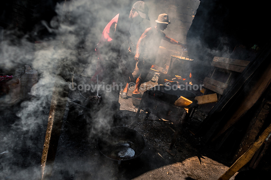 Afro-Colombian cooks fry fish in boiling oil in a street restaurant in the market of Bazurto in Cartagena, Colombia, 16 December 2017. Far from the touristy places in the walled city, a colorful, vibrant labyrinth of Cartagena's biggest open-air market sprawls to the Caribbean seashore. Here, in the dark and narrow alleys, full of scrappy stalls selling fruit, vegetables and herbs, meat and raw fish, with smelly garbage on the floor and loud reggaeton music in the air, the African roots of Colombia are manifested.