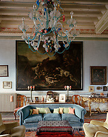 In the entrance hall a colourful 18th-century Murano glass chandelier hangs above a cosy seating area surrounded with pieces from Moreno Petrini's collection of local antique furniture