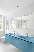 A chic, blue, double basin with slic handleless drawers hovers under glass fronted cabinets in this bathroom