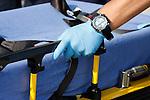 An EMT hand on a medical transport cot