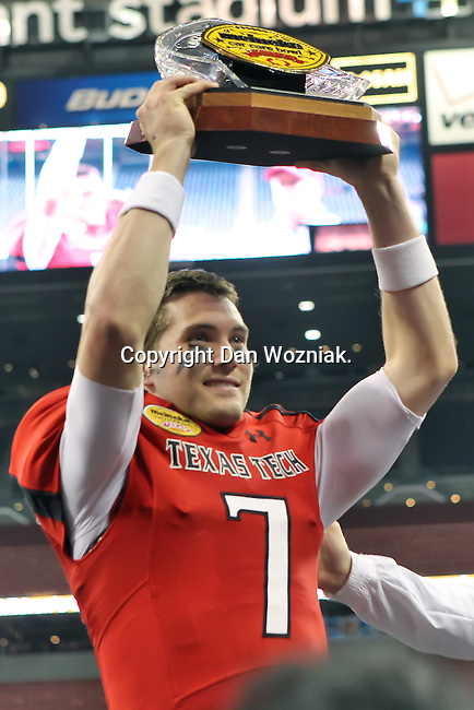 Texas Tech Red Raiders quarterback Seth Doege (7) holds up the MVP trophy after the Meineke Car Care Bowl game of Texas between the Texas Tech Red Raiders and the Minnesota Golden Gophers at the Reliant Stadium in Houston, Texas. Texas defeats Minnesota 34 to 31.