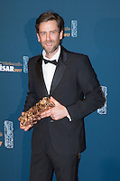 """French production designer Jeremie D. Lignol poses during a photocall after winning the Best Set design award for """"Chocolat"""" during the 42nd edition of the Cesar Ceremony at the Salle Pleyel in Paris on February 24, 2017."""