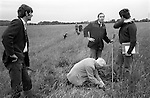 Yarnton Meadow Mowing Rights. Eddie Harris Meadows Man, and farmer at Paternoster Farm, Yarnton, cutting initials in turf to signify who owns the land for the coming year. William Carter who looks after the steam train at  Paternoster Farm (centre with sticks).<br />