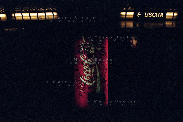 Milano, stazione della metropolitana linea 3. Un distributore di lattine Coca-Cola coperto di graffiti e l'immagine di un volto su una pubblicità --- Milan, station of subway line 3. A dispenser of Coca Cola cans covered with graffiti writings and the image of a face on an advertising
