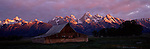 Moulton barn sits below the Tetons as the sun rises in Grand Teton National Park, Wyoming.