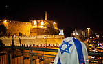 An Israeli youth covered with the flag of Israel looks at traffic next to the David citadel in Jerusalem Wednesday May 28 2014, during celebrations marking Jerusalem day. The Day marks the reunification of Jerusalem following the 1967 Six Day War when Israel captured the Arab part of the city from Jordan. Photo By Eyal Warshavsky