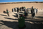 A group of villagers gathers around as an elder speaks to a U.S. soldier and an interpreter in the Shah Joy district of southern Afghanistan's Zabul province. U.S. and NATO strategy in Afghanistan now emphasizes protecting villagers over pursuing and killing the Taliban. Oct. 25, 2009. DREW BROWN/STARS AND STRIPES