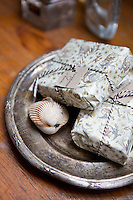 Carefully packaged homemade soap is displayed on a nickel silver dish in the bathroom