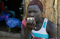 ETHIOPIA Province Benishangul-Gumuz, town Debate, Gumuz village Banush, Gumuz woman drink coffee / AETHIOPIEN, Provinz Benishangul-Gumuz, Stadt Debate, Gumuz Dorf Banush, Gumuz Frau trinkt Kaffee