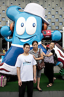 China. Shanghai. World Expo. Expo 2010 Shanghai China.  China Pavilion. A chinese family, all tourists, an old woman and a couple, stand and pose for a picture in front of Haibao, which is the name of the mascot of World Expo 2010 Shanghai China. Hai Bao means the treasure of the sea. The name of Hai Bao is easy to remember, echoes with the color of its body and is a typical lucky name in Chinese tradition. Hai Bao is the good well ambassador of Shanghai Expo and is embracing friends from all over the world with his arms and confident smile.  25.06.10 © 2010 Didier Ruef