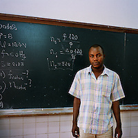 26-year-old electronic engineering student Sebastiao standing in front of a blackboard at the Agostinho Neto University (Universidade Agostinho Neto).