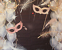 Backdrop featuring masks, feathers and beads for masquerade gala party