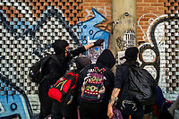 Radical students of the Universidad Nacional de Colombia attach a poster onto the wall during a protest march against government's policies and corruption within the public educational system in Bogotá, Colombia, 24 October 2019.