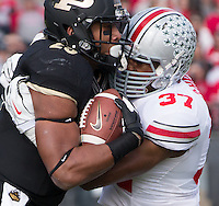 Ohio State linebacker Joshua Perry (37)  tackles Purdue running back Brandon Cottom (25). The Ohio State Buckeyes defeated the Purdue Boilermakers 56-0 at Ross-Ade Stadium, West Lafayette, Indiana on November2, 2013.