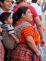 Antigua, Guatemala.  Maya Mother in Traditional Clothing with Son on her Back.  Semana Santa.