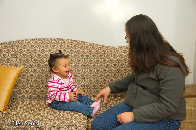 MR / Schenectady, NY. Infant (girl, 12 months, African American & Caucasian) laughs as her mother (21) plays with her. MR: Dal4. ID: AL-HD. © Ellen B. Senisi