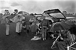 Bad weather Uk 1980s people at Cowdray Park Polo Club 1981 getting wet alfresco picnicking during lunch break UK