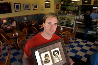Dan McCauley holds high school graduation photos of his grandmother (l) and mother which are displayed in his restaurant, A Taste of Heaven.
