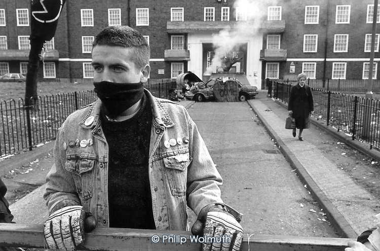 A masked squatter waits to be evicted by Hackney Council bailiffs in front of a burning car barricade on Stamford Hill Estate, London.