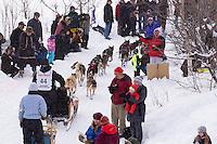Aaron Burmiester runs the gauntlet of spectators along the bike trail near the Alaska Native Hospital during the  Ceremonial Start of Iditarod 2012 in Anchorage, Alaska.