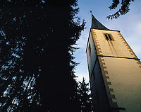 Dramatic low-angle view of church steeple in a gap in dark trees, River Neckar valley, Bavaria, southern German
