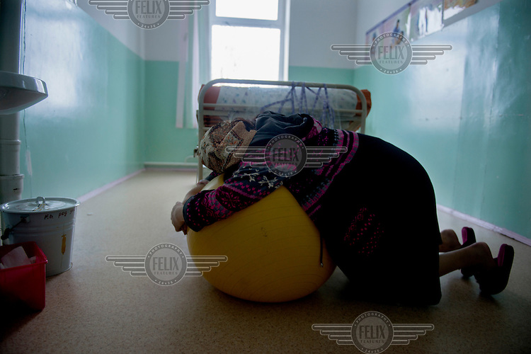 Dinara lies across a large plastic ball as she tries to get comfortable and reduce the pain of her labour. Her labour started at home nine hours before and she has come to the hospital in Naryn to give birth. Dinara ia a 'forced bride'. She was kidnapped by a teacher, Ahmat, in October 2012 just 10 days after they first met each other. Although illegal, bride kidnapping is common in rural parts of Kyrgyzstan. Each year around 16,000 women become married after being kidnapped. They are known as 'Ala Kachuu' that translates as 'to grab and run away'. Defenders of the continuation of the practice sight tradition. However, during Soviet Times it was rare, and parents generally arranged marriages.