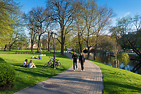 People walk and sit on the lawn in Bastion Hill Park historic place in Riga, Latvia