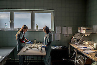 Victoria Amina-Dautovic (right) and Bojana Tomasevic, staff at an International Commission on Missing Persons (ICMP) mortuary facility, train using a synthetic skeleton.
