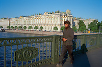 Saint Petersburg, Russia, June 2002..A homeless man walks over he River Neva in front of the Hermitage, former home of the Tsars, and one of the world's great museums..